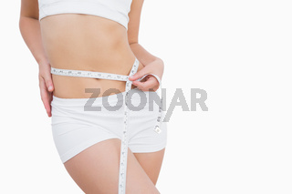 Fit woman measuring waist with measuring tape