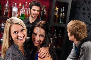 Girl friends at the bar hugging together