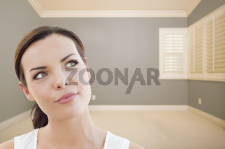 Daydreaming Young Woman in Empty Grey Room