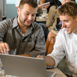 Men business partners working on laptop cafe