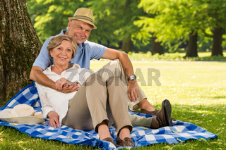 Happy pensioners hugging and relaxing outdoors
