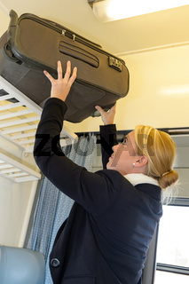 Woman putting her luggage on train grid