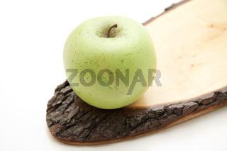Apfel auf Holzteller mit Rinde