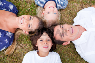 Cheerful family lying in circle on the grass