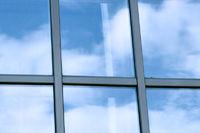 clouds in glazed panel skyscraper