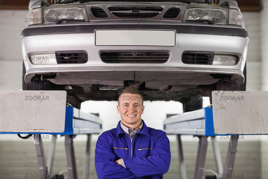 Mechanic with arms crossed below a car
