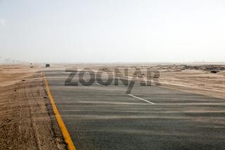 Einsamer Wagen auf Sand verwehter Wüstenstrasse