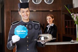 Concierge im Hotel hält Service-Schild