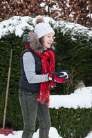 Blond teenager girl making a snowball in snowy back yard