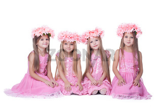 Four little girls with long hair in pink dresses