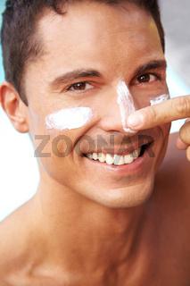 Lachender Mann cremt Gesicht ein