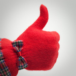 thumb up in red glove over grey background