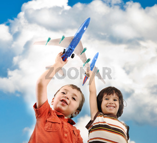 Two small boys with airplains in hands