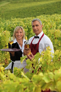 Man and woman serving white wine in a vineyard