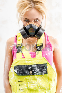 Female wearing coverall, hardhat and respirator posing over obsolete wall