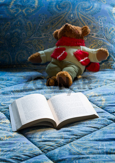 Paperback book open on bed with teddy bear
