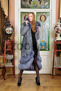 beautiful woman in fur coat in the  luxurious classical interior.