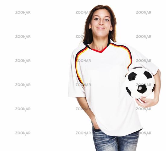 lachende junge frau in fussball trikot mit fußball unter dem arm