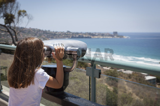 Young Girl Looking Out Over the Pacific Ocean with Telescope