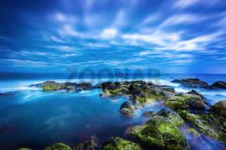 Dusk over calm blue sea over ocean and cloudy sky