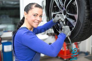 Kfz Mechatronikerin beim Reifenwechseln an Hebebühne