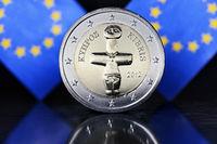Zwei-Euro-Münze von Zypern und EU-Fahnen
