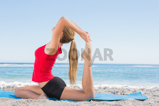 Fit blonde stretching leg in yoga pose