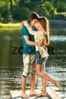 Embracing teens standing barefoot on pier