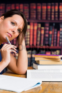 Cute woman thinking with pen and book