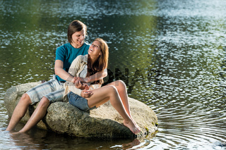 Couple sitting on rock by the lake