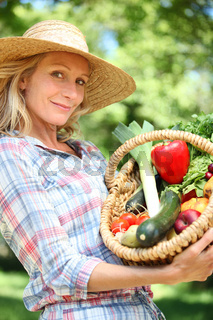 Woman holding basket of vegetables.