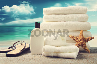 Lotion, towels and sandals with ocean scene