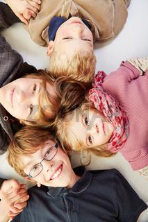Lachende Kinder liegen im Kreis