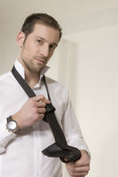 Junger Mann bindet eine Krawatte