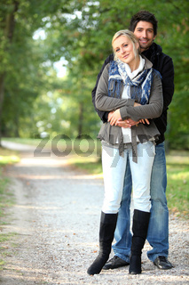 Couple hugging on a forest path