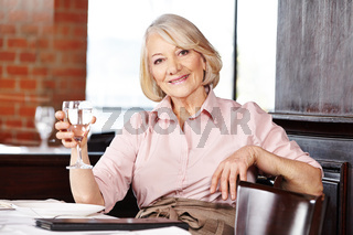 Seniorin trinkt Wasser im Restaurant