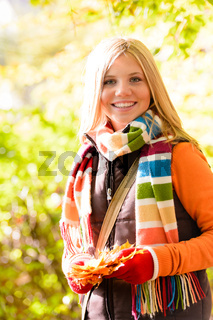 Sunny autumn smiling girl holding dry leaves