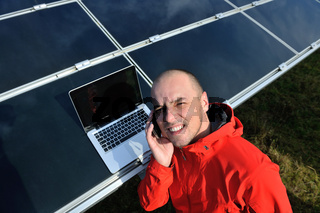 engineer using laptop at solar panels plant field