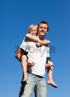 Smiling father with his son on his back outdoor