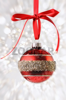 Red Christmas ball with ribbon on sparkly background