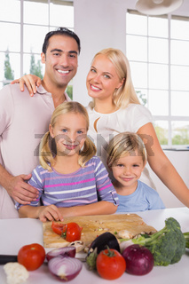 Posing family cutting vegetables together