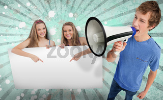 Pretty girls pointing to copy space with young man shouting through megaphone