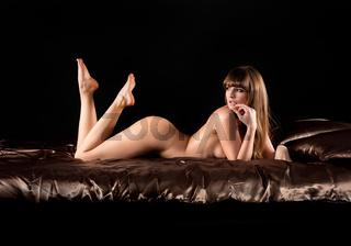 Nackte blonde junge Frau im Bett mit brauner Seide