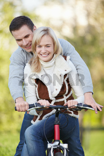 Young couple rides a bicycle in the park