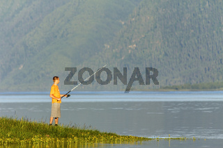 The lonely fisherman with fishing tackle in hands