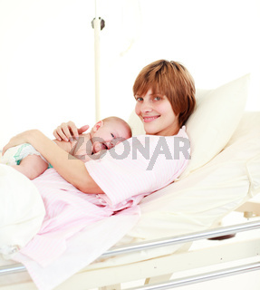 Patient with newborn baby in bed smiling at the camera