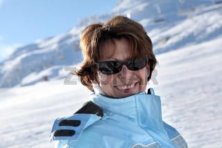 Middle-aged woman stood on snowy mountain
