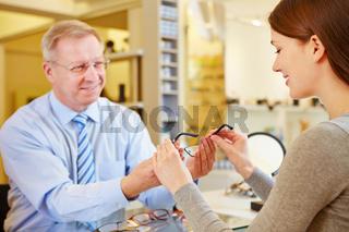 Junge Frau kauft Brille beim Optiker