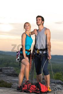 Rock climbing active couple on top sunset