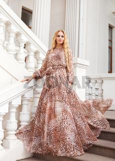 Beautiful blond woman in long dress outdoors